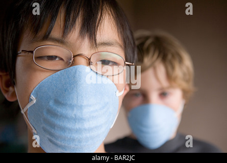 closeup of two children, ages 12 and 10 wearing masks - Stock Photo