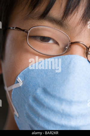 closeup of japanese twelve year old boy wearing a mask - Stock Photo