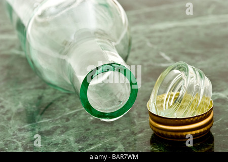 Glass bottle cut off at the neck with a golden bottle cap - Stock Photo