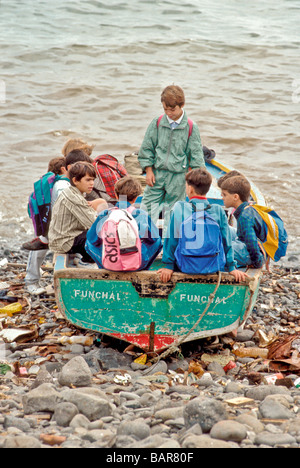 Children playing in a canoa class inshore fishing boat on beach at Canical Madeira island Portugal Atlantic Ocean - Stock Photo