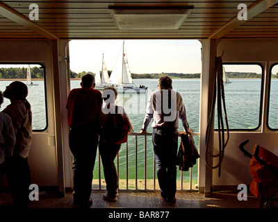 Passengers looking across the Water to Sailing Boats from a Passenger Ferry on the Chiemsee Chiemgau Bavaria Germany - Stock Photo
