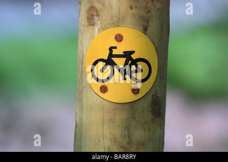 Cycle route sign on a wooden post, waymarking a mountain bike route - Stock Photo