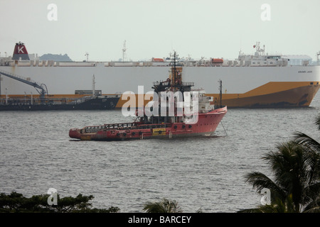 A fire boat with a backdrop of an Italian car carrier ship off the southern coast of Sentosa Island Singapore with - Stock Photo