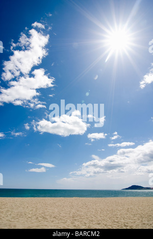 Sun shining on the beach with blue sky and clouds - Stock Photo