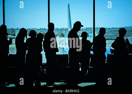 Travelers standing in line at the airport waiting to board an airplane - Stock Photo