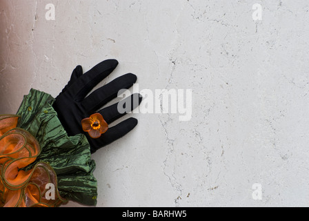 Close up of a hand with orange flower ring of Venice disguise in front a wall flower ring of Venice disguise in - Stock Photo