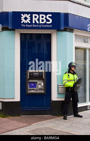 Police officer in riot gear guards RBS bank during protests in Brighton, Sussex, UK JPH0203 - Stock Photo