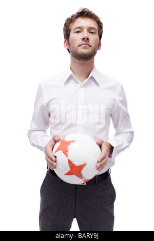 Young man holding soccer ball, portrait - Stock Photo