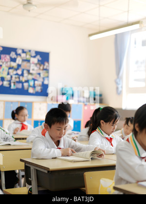 A classroom of young students reading a lesson from their textbook - Stock Photo