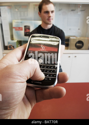 trying a blackberry RIM smart phone in Vodafone store - Stock Photo