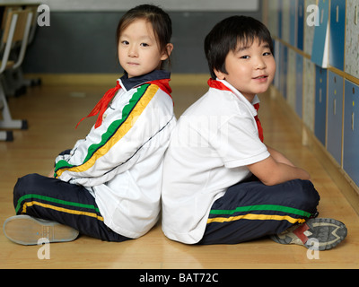 Two classmates sitting Indian-style on the floor of their classroom. - Stock Photo