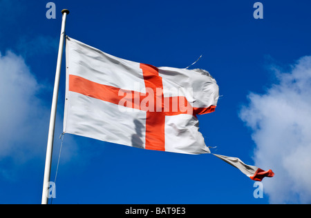 A torn flag of St George the English patron saint. - Stock Photo