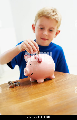 Child with loose change. Young boy saving money from an early age. He is sixyears old. - Stock Photo