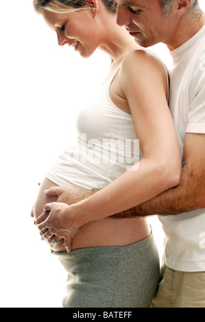 Expectant parents. Happy pregnant woman and her partner resting their hands on herswollen abdomen. - Stock Photo