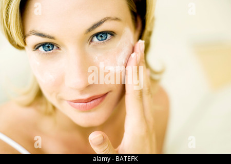 Anti-wrinkle cream. Woman with dots of cream on the wrinkles around her eye. - Stock Photo