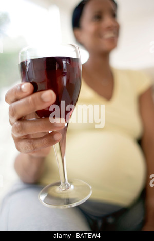 Pregnant woman with a glass of redwine. She is at full term. - Stock Photo