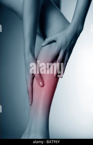 Lower leg pain, conceptual image.Woman massaging her sore calf. - Stock Photo