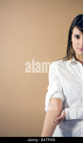 young woman with band-aid on arm - Stock Photo