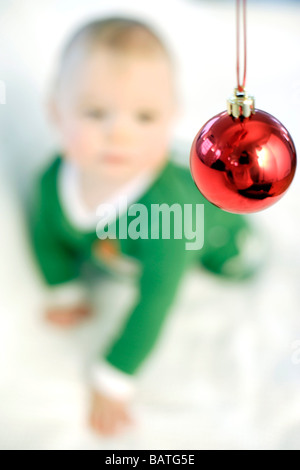 Baby boy looking at a Christmas bauble. He is nine months old. - Stock Photo