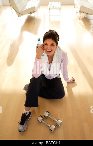 Woman resting on the floor after exercising. - Stock Photo