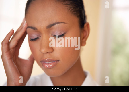 Headache. Woman with a headache holding her painful head. Headaches are generally caused by the expansion of blood - Stock Photo