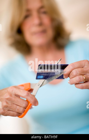 Credit card debt. Woman using a pair of scissors to cut up her credit card. - Stock Photo
