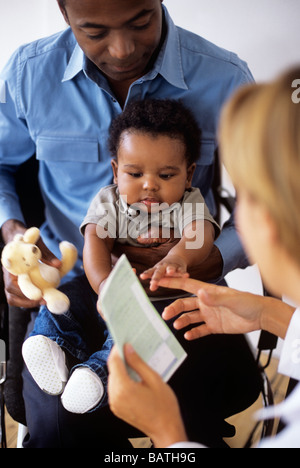 Paediatric examination. Doctor holding a prescription while she examines a 5-month-old boy sitting in his father - Stock Photo