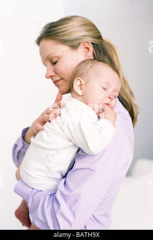 Mother and baby. Mother holding her sleeping baby daughter who is sucking her thumb. - Stock Photo