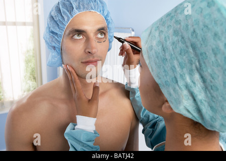 Cosmetic surgery. Cosmetic surgeon preparing a patient for cosmetic surgery. - Stock Photo