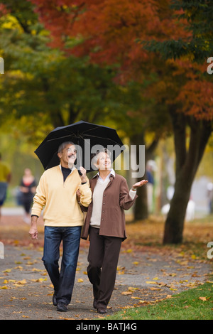 African couple walking with umbrella in autumn