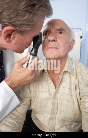 Eye examination. Doctor using an ophthalmoscope during an eye examination. - Stock Photo
