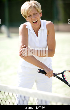 Painful elbow injury. Woman holding her elbow in pain during a game of tennis. - Stock Photo