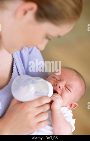 Mother bottle-feeding baby. Mother using a bottle to feed milk to her 2-month-old baby boy. - Stock Photo