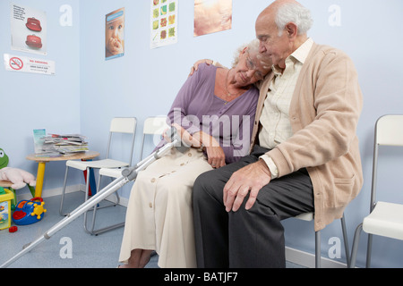 Elderly couple comforting each other in a general practice waiting room. - Stock Photo