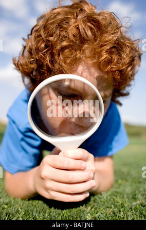 Boy using a magnifying glass to examine an area of grass. - Stock Photo
