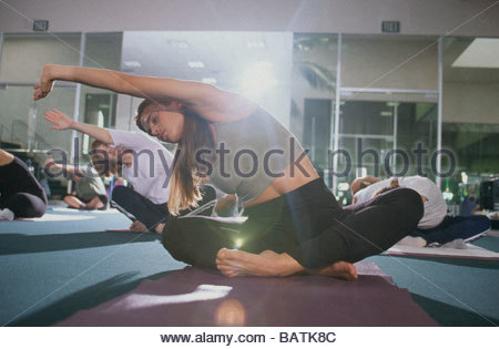 Woman stretching in yoga class - Stock Photo