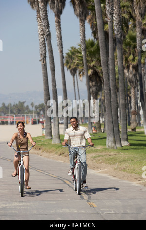 Young couple riding bicycles at beach - Stock Photo
