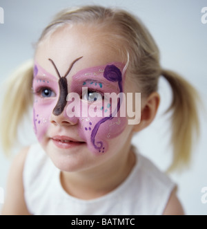 Face painting. 3-year-old girl who has had her face painted with a butterfly pattern. - Stock Photo