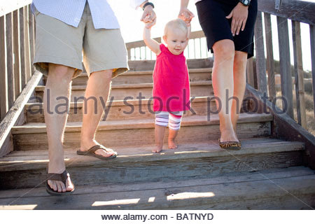 Mother and father walking baby girl down steps - Stock Photo