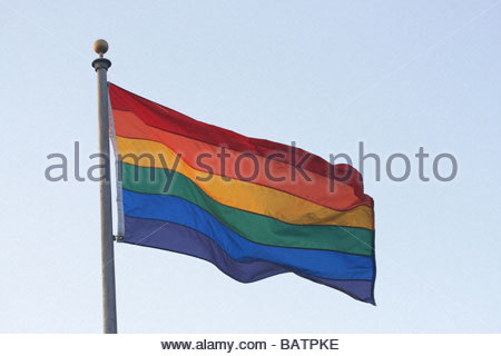 Rainbow flag blowing in wind - Stock Photo