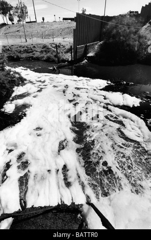 The New River US Mexico border Calexico USA . Polluted water from an outflow joins the New River running past the - Stock Photo