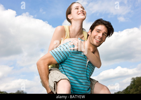 portrait of young man giving girlfriend piggyback ride - Stock Photo