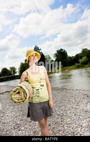 young woman with yellow hat walking along river in summer - Stock Photo
