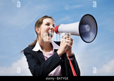 portrait of young businesswoman shouting through megaphone - Stock Photo