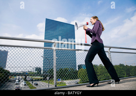 young businesswoman standing on bridge shouting through megaphone - Stock Photo