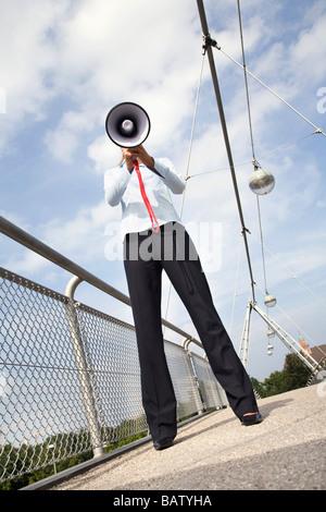 young businesswoman standing on bridge hidden behind megaphone - Stock Photo