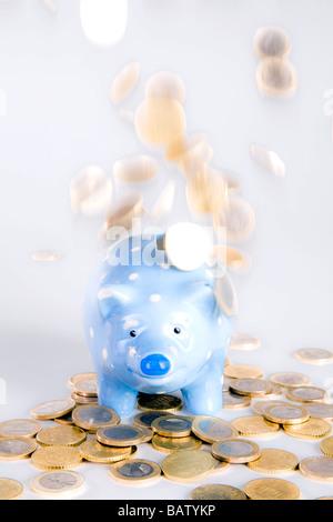 euro coins raining down on blue piggybank - Stock Photo