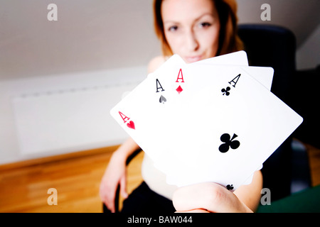 young woman with playing cards showing four aces - Stock Photo