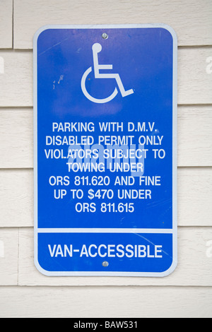 A parking with permit only sign for handicapped and wheelchair bound people - Stock Photo