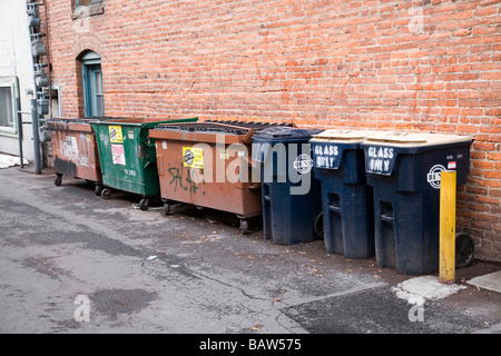 A group of garbage cans containers dumpsters and recycle bins in an alley - Stock Photo